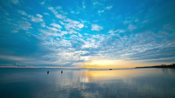 一望无际的湖面上反射落日余晖的实拍视频