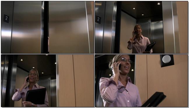 公司秘书边打电话边走出电梯的实拍视频
