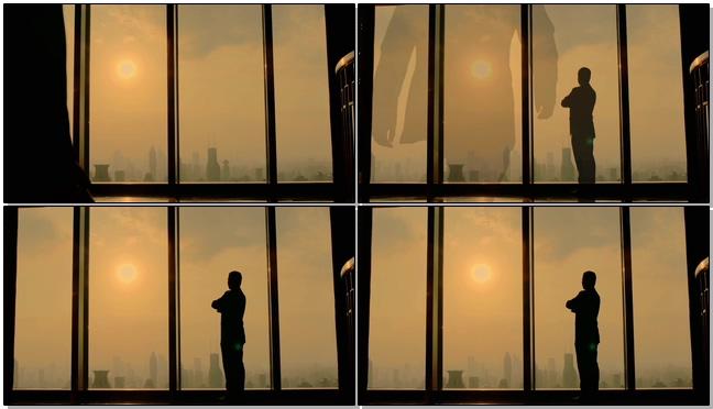 公司老板站在窗前看日落的实拍视频