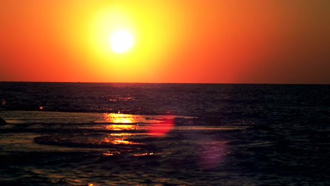 唯美梦幻的红色落日悬挂在海上的实拍视频